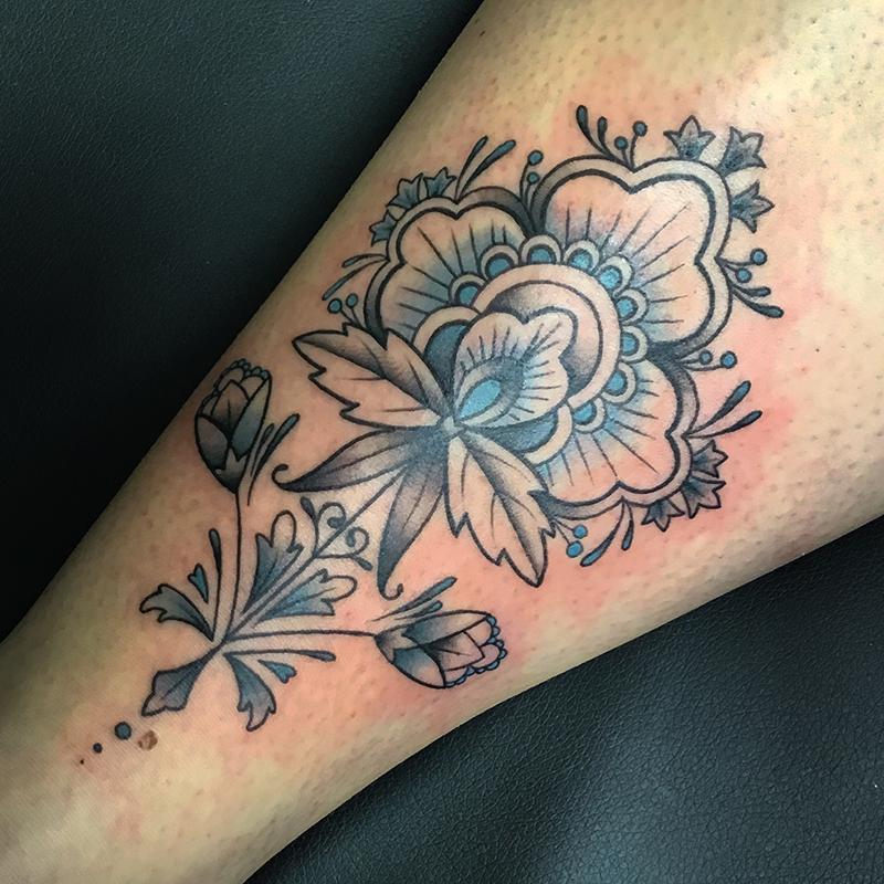 floral blackwork tattoo with blue details
