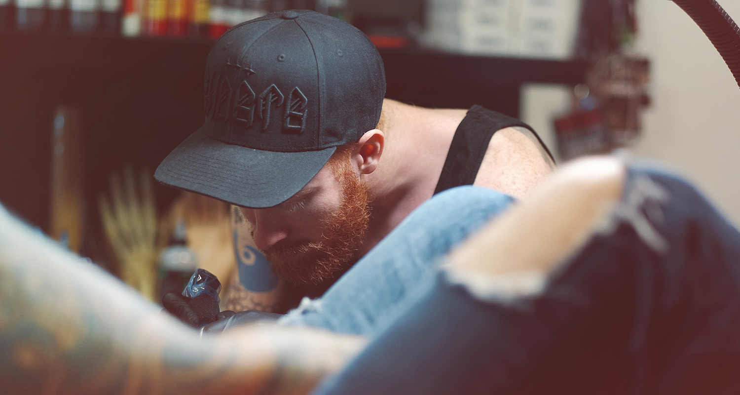 photo of Michael Cloutier tattooing a client