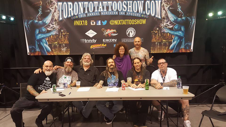 Damien Mcgrath at table with judges at toronto tattoo festival